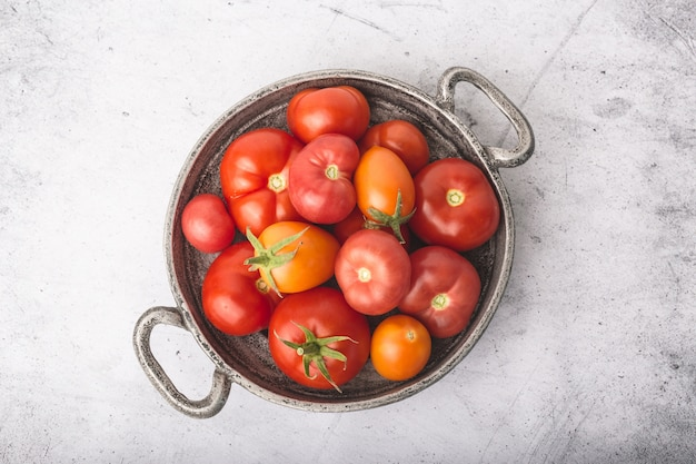 Juicy, ripe tomatoes in metal bowl with bunches on stone table