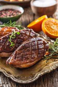 Juicy roasted duck breasts on a vintage table with rosemary, cut orange, salt and pepper.