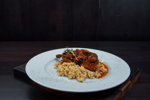 레스토랑의 나무 빈티지 테이블에 바비큐 소스와 함께 죽과 육즙 구운 오리 고기. 뜨거운 맛있는 음식. 확대