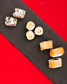 Juicy salmon rolls and sushi on black stone plate over red surface
