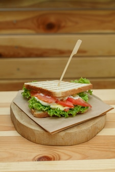 Juicy sandwich with bacon, fresh vegetables, green salad and dark lines after grill on wooden plate