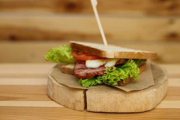 Juicy sandwich with grilled bread and bacon wait for you on wooden plate