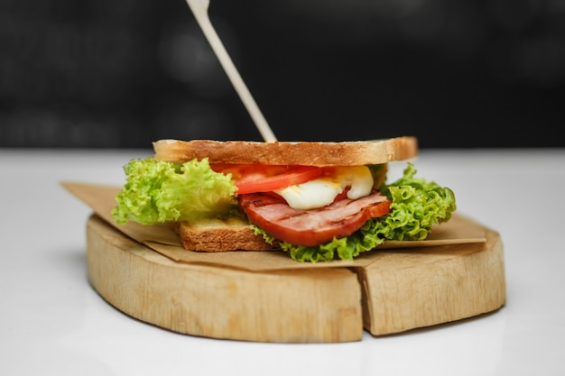 Juicy sandwich with grilled bread and bacon on wooden plate