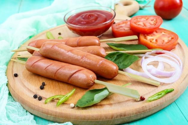 Сочные сосиски на шпажках с помидорами и томатным соусом на круглой доске