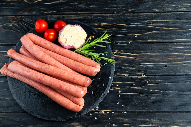 Juicy sausages on a stone chopping board with rosemary and spices, pepper and coarse salt