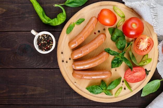 Сочные колбаски с помидорами и базиликом на круглой разделочной доске на темном деревянном столе