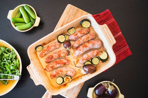 Juicy sausages with vegetables on baking pan