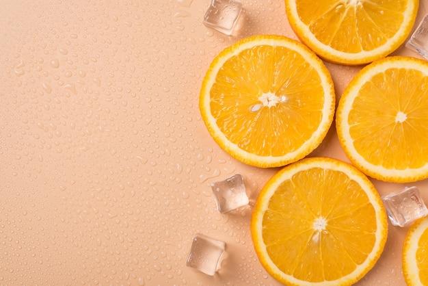 ジューシーな季節の夏のスパのコンセプト。頭上のフラットレイの上の上にテキストの空の空白スペースのための場所とオレンジ色の果物と角氷のおいしいおいしいスライスのクローズアップ写真
