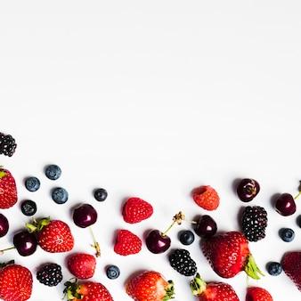 Juicy seasonal berries on light surface