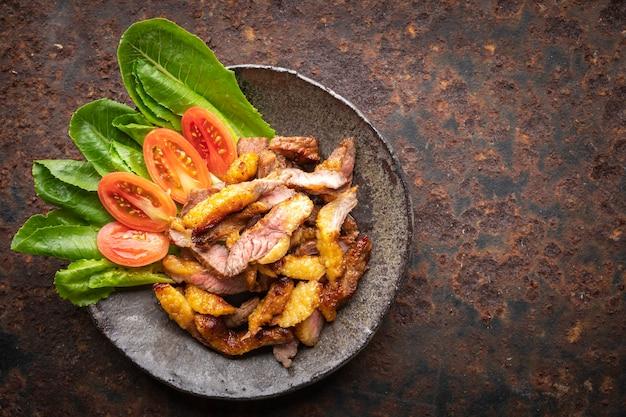 녹슨 질감 배경에 있는 와비 사비 접시에 즙이 많은 얇게 썬 그릴 비프 필레 스테이크 고기, 텍스트 복사 공간, 위쪽 전망