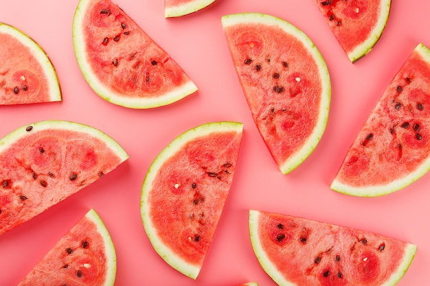 Juicy slices of red watermelon on a bright pink . ual colors of summer. patterns top view as a  or substrate