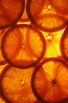 Juicy slices of ripe orange with backlight in the form of cut rings