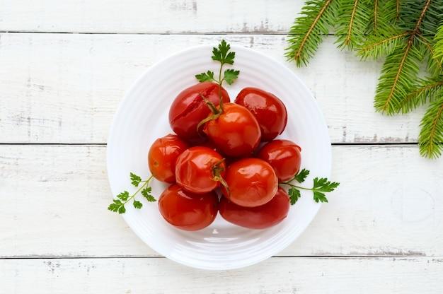 白いプレートにジューシーでスパイシーなマリネしたトマト、上面図。