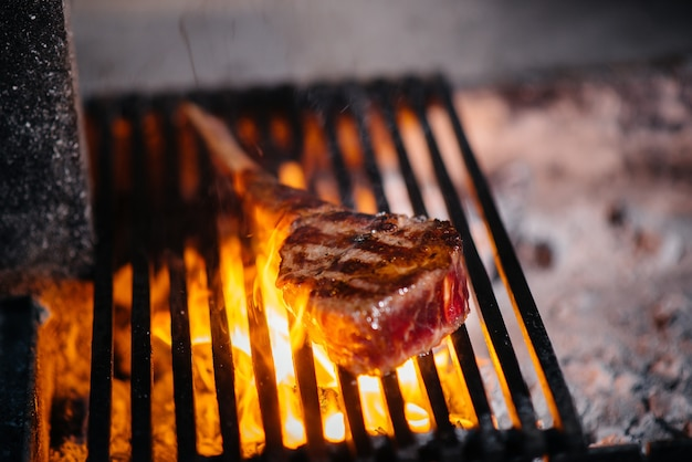 육즙이 풍부한 스테이크는 레스토랑에서 구워집니다. 그릴에 불에 고기를 굽고 있습니다.