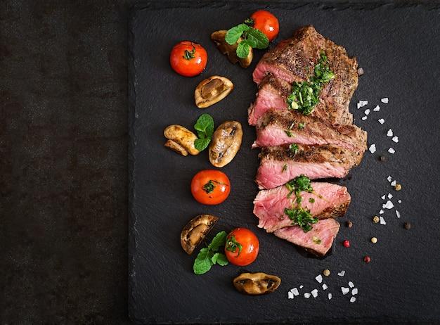 Bistecca succosa mediamente rara di manzo con spezie e verdure grigliate.