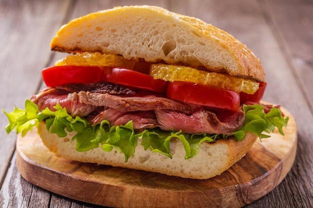 Juicy steak sandwich with vegetables and slices of orange.