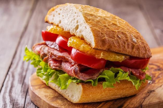 Juicy steak sandwich with vegetables and slices of orange