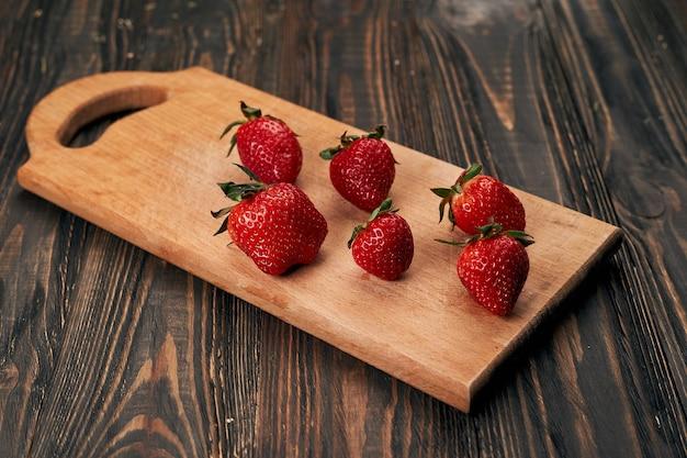 Сочная клубника на деревянной кухонной доске