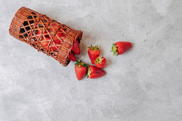 Juicy strawberries poured out chaotically on a concrete light wall. delicious fruits in summer season. natural products and natural resources.