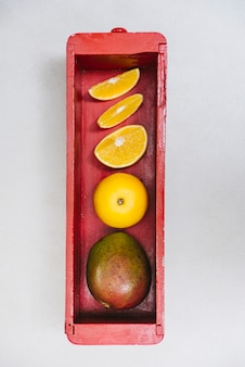 Juicy sweet lime and mango in wooden container on white background