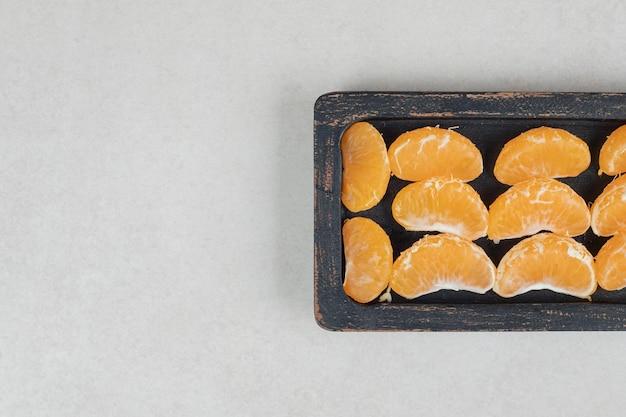 Segmenti succosi del mandarino sulla banda nera