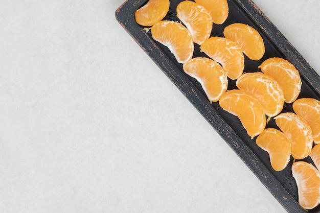 Succosi segmenti di mandarino su banda nera
