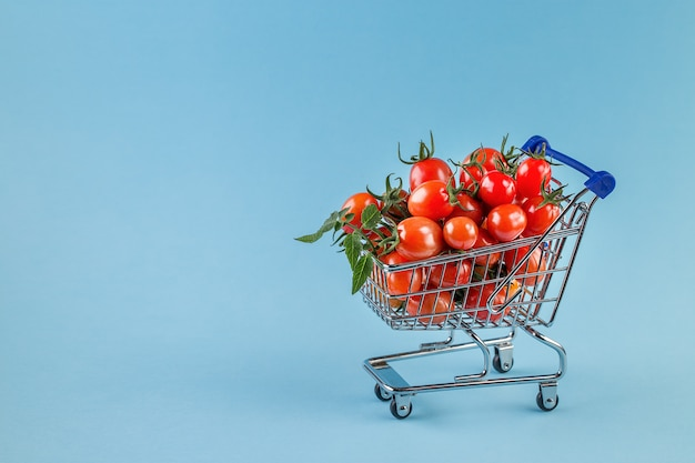 Juicy tomatoes in shopping cart on blue background.