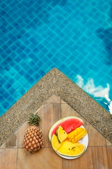 Juicy tropical fruits set at pool edge with crystal blue water. luxury weekend rest.