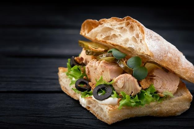 Сочный бутерброд с тунцом с сыром, салатом и оливками