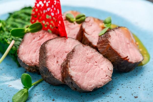 黒い表面にほうれん草とマスタードソースを添えたジューシーな子牛のステーキ