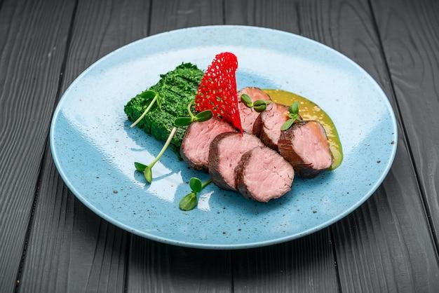黒にほうれん草とマスタードソースを添えたジューシーな子牛のステーキ