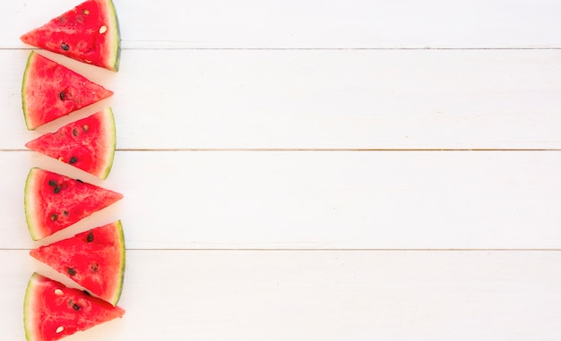 Juicy watermelon slices design on wooden white plank backdrop