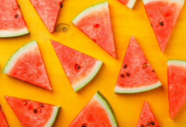 Juicy watermelon slices on a yellow wooden background.