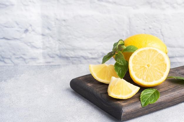 Сочные желтые лимоны целиком и нарезанные свежими листьями мяты