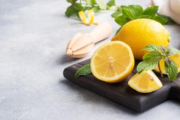 ジューシーな黄色いレモン全体と新鮮なミントの葉でカット
