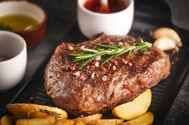 로즈마리, 마늘, 감자와 프라이팬 팬에 수분이 많은 뉴욕 스트립 스테이크, 클로즈업, 선택적 포커스