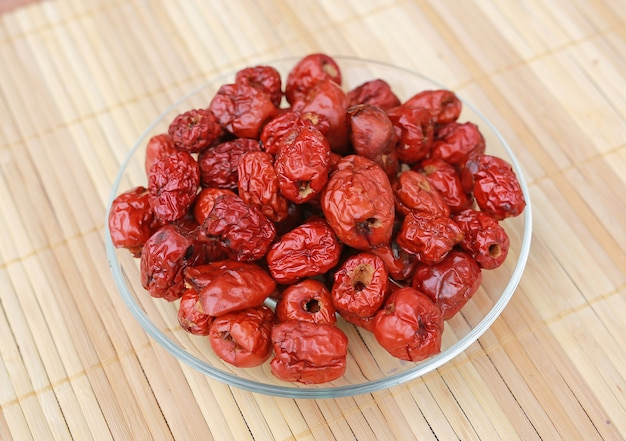 Jujube, chinese dried red date fruit on a plate against wood background.