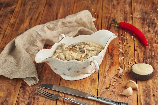 Жульен с курицей, грибами и сыром в керамической миске на деревянном столе
