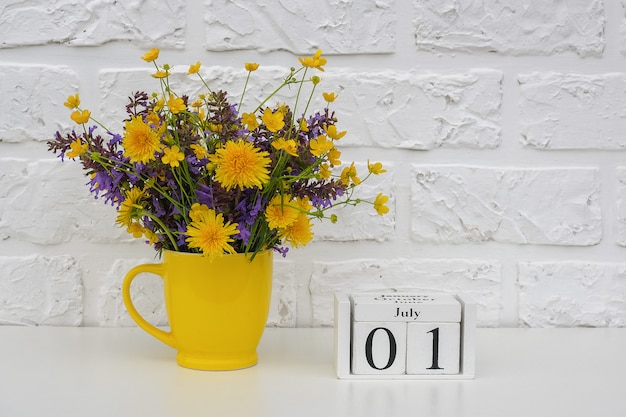 July 1 and yellow cup with bright colored flowers against white brick wall.