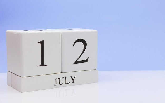 July 12st. day 12 of month, daily calendar on white table with reflection, with light blue background.
