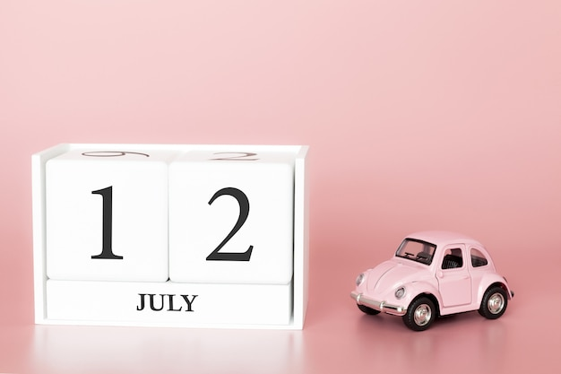 July 12th, day 12 of month, calendar cube on modern pink background with car