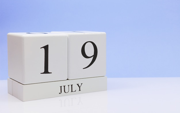 July 19st. day 19 of month, daily calendar on white table with reflection, with light blue background.