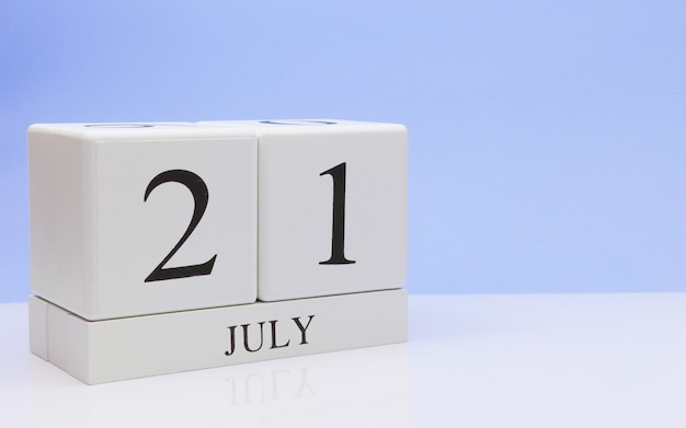 July 21st. day 21 of month, daily calendar on white table with reflection, with light blue background.