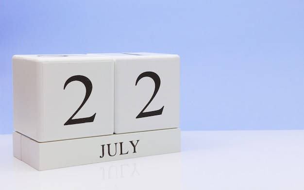 July 22st. day 22 of month, daily calendar on white table with reflection, with light blue background.