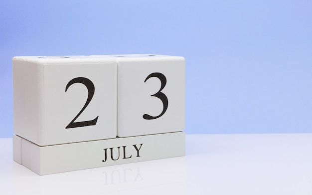 July 23st. day 23 of month, daily calendar on white table with reflection, with light blue background.
