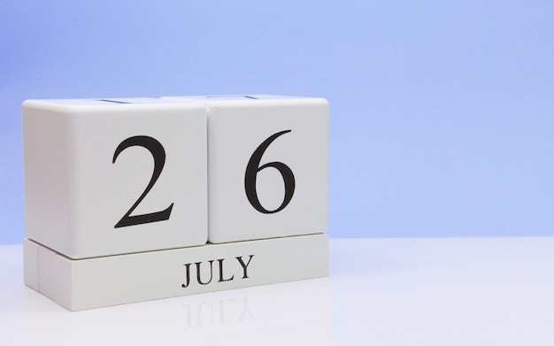July 26st. day 26 of month, daily calendar on white table with reflection, with light blue background.