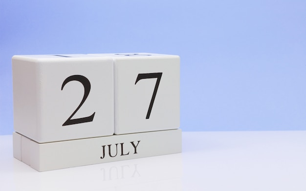 July 27st. day 27 of month, daily calendar on white table with reflection, with light blue background.