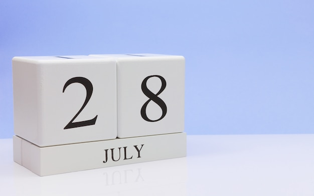 July 28st. day 28 of month, daily calendar on white table with reflection, with light blue background.