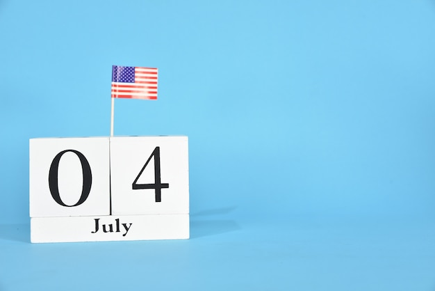 July 4 text wooden block calendar and american flag on blue