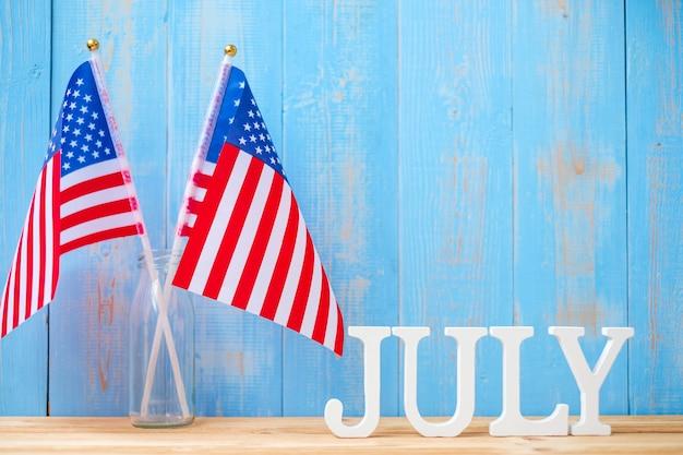 7月のテキストと木製のテーブルの背景にアメリカ合衆国の旗。独立とお祝いの概念の米国の休日